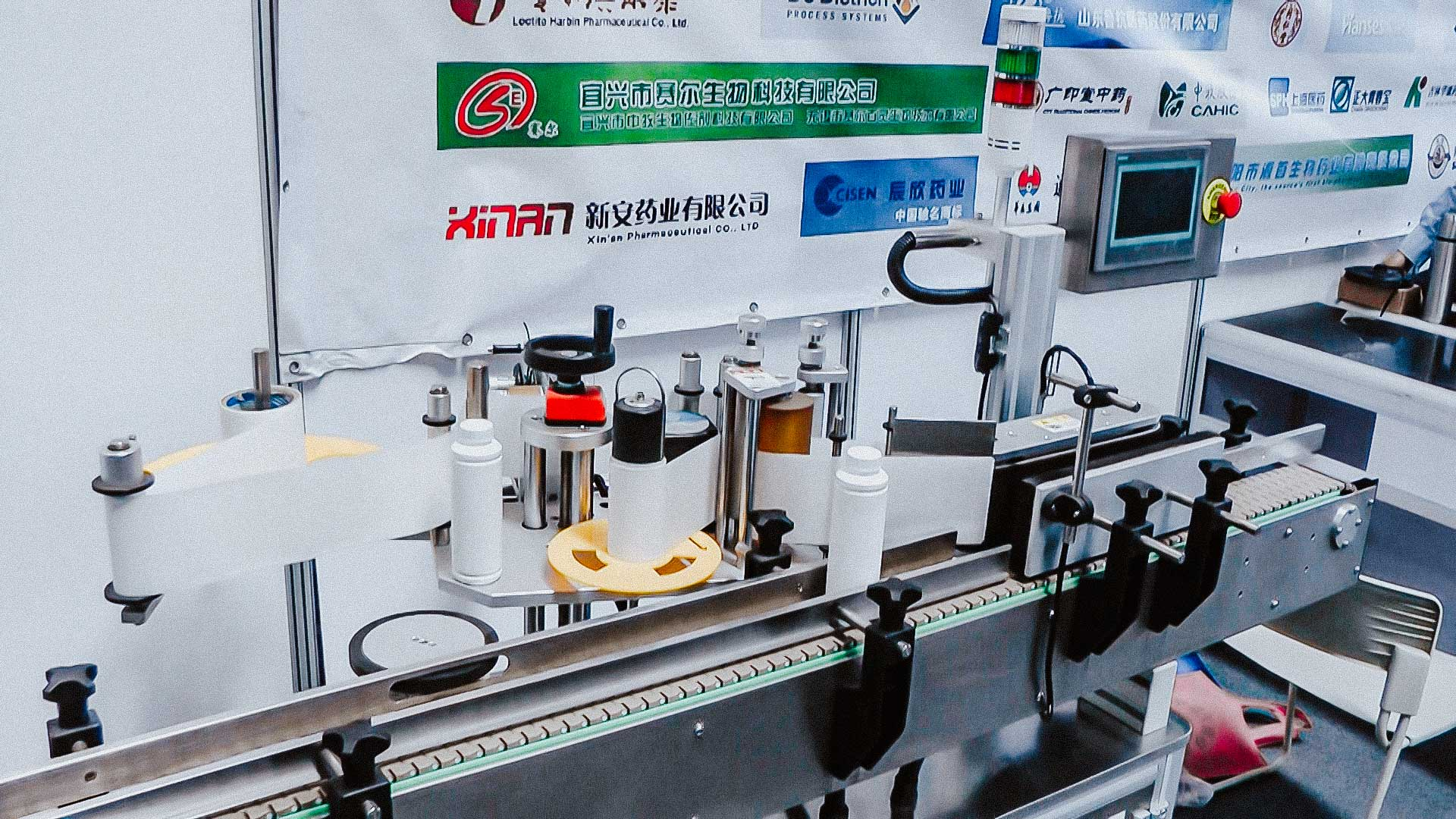 Automatic equipment for self-adhesive labels on round plastic bottles