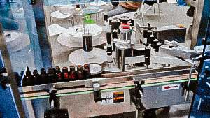 Automatic labeling machine for labelling labels on glass bottles