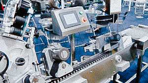 Automatic labeling machine for sticking labels on glass ampoules and vials
