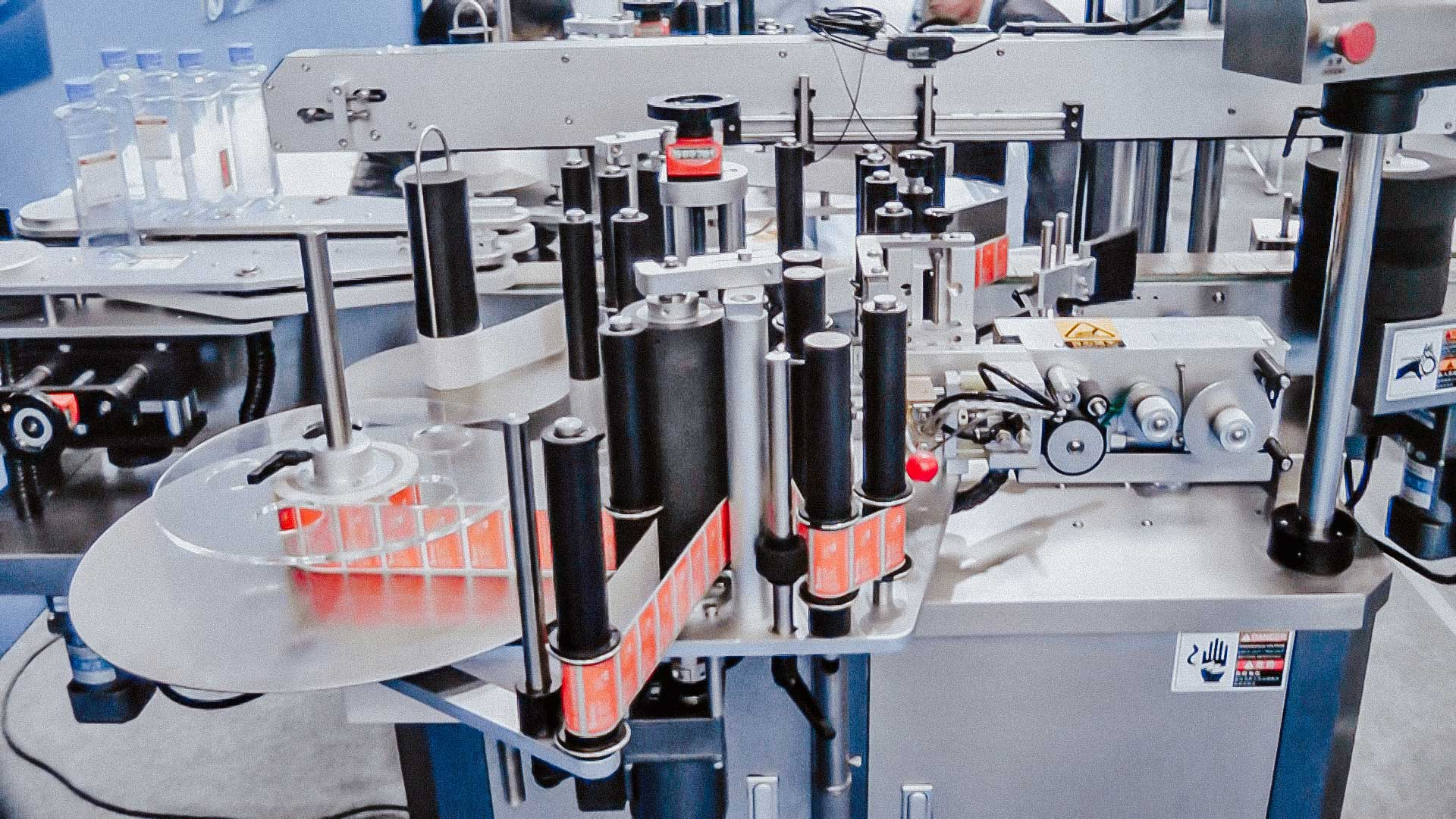 Automatic labeling machine for sticking labels on square bottles on both sides