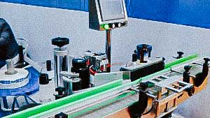 Automatic labeling machine for sticking self-adhesive labels on glass bottles with syrup