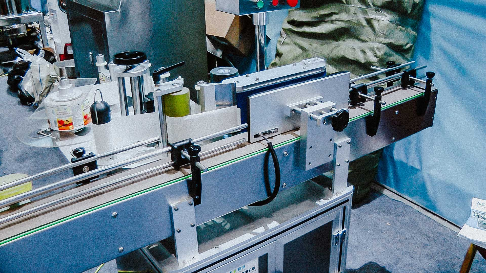 Automatic labeling machine for sticking self-adhesive labels on glass bottles