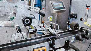 Labeling machine for sticking self-adhesive labels on top of caps and boxes