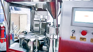 Automatic equipment for filling hard gelatine capsules with granules