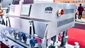 Automatic equipment for screwing plastic caps on plastic bottles