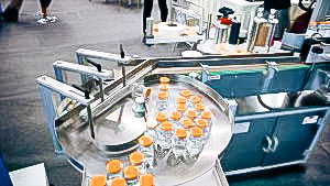 Automatic equipment for sticking self-adhesive labels on the glass bottles