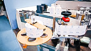 Automatic labeling equipment for sticking labels on both sides of flat bottles