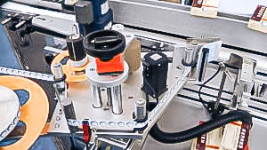 Automatic equipment for sticking self-adhesive labels on cardboard boxes of pharmaceutical production