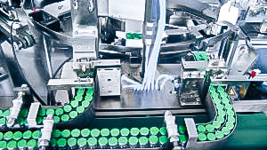 Automatic packaging equipment penicillin vials in cardboard boxes in pharmaceutical production